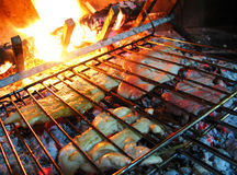 Cooking meat. Meat on the grill cooking on fire Stock Photos