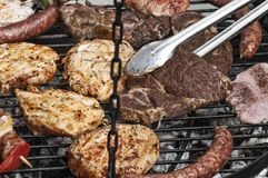 Cooking meat on the barbecue grill. Hand cooking at grill with various delicious barbecue outdoor, selective focus Royalty Free Stock Photos