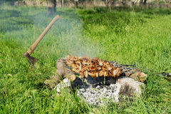 Cooking meat barbeque on the firepit. Preparing pork BBQ, rocks are used as mangal. Fireplace is placed in the center of green grass lawn. Axe used to cut royalty free stock photography