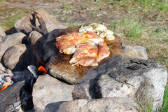 Cooking Meat on Bonfire. Raw peace of chicken meat heating on bonfire on a flat stone Stock Photo