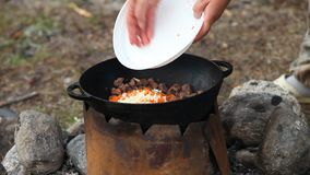 Cooking of meat in cauldron outdoors stock video footage