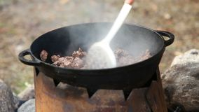 Cooking of meat in cauldron outdoors stock video