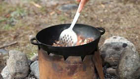 Cooking of meat in cauldron outdoors stock footage