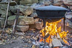 Cooking meat on a fire in cast-iron cauldron. Cooking meat outdoors in cast-iron cauldron. Cooking meat on a fire. Food in a cauldron on a fire. Cooking food in Royalty Free Stock Image