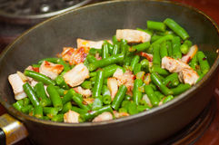 Cooking meat with green beans in pan Stock Images