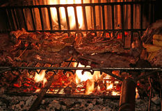 Cooking the meat on the grill in the fireplace. Cooking the meat on the grill in the big fireplace in the restaurant royalty free stock images