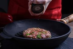 Cooking meat on grill pan. Women`s hands sprinkle pepper with spices cutlet.  royalty free stock photos