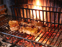 Cooking the meat grilled chicken in the large fireplace Stock Photography