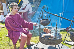 Cooking meat in a medieval re-enactment. Young man turning a spit over the fire to cook a leg of pork in a re-enactment  called  Through the centuries Stock Photos