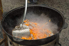 Cooking meat outdoors in cast-iron cauldron. On a fire. Food in . in nature the Stock Photo