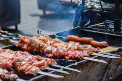 Cooking meat and sausages on skewers. Shashlik on coals Stock Image