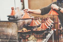 Cooking of meat in traditional Moroccan ceramic tajine dish, Mar Stock Photos