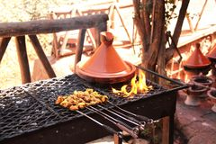 Cooking of meat in traditional Moroccan ceramic tajine dish, Mor Royalty Free Stock Image