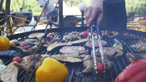 Cooking of meat and vegetables on the grill. Hand using tongs for turning meat on the barbecue. Sausages, chicken, bell pepper, eggplant, tomatoes are fried on stock video
