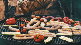 Cooking of meat and vegetables on the grill. Hand using tongs for turning meat on the barbecue. Sausages, chicken, bell pepper, eggplant, tomatoes are fried on stock footage