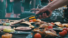 Cooking of Meat and Vegetables on the Grill. Hand Using Tongs For Turning Meat on the Barbecue. Sausages, chicken, bell pepper, eggplant, tomatoes are fried on stock video footage