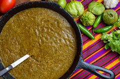 Cooking Mexican green sauce, salsa verde asada, flat lay. Cooking Mexican green sauce, salsa verde, made with tomatillos, tomatoes, onions, garlic chiles and stock photos