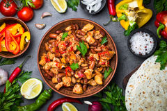 Cooking Mexican taco with meat beans and vegetables. Cooking Mexican taco with meat beans and vegetables at black slate table. Latin american food background stock photo