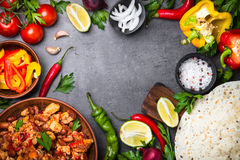 Cooking Mexican taco with meat beans and vegetables. Cooking Mexican taco with meat beans and vegetables at black stone table. Latin american food background Royalty Free Stock Images