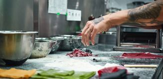 Cooking moments. Cropped image of chef`s hands with beautiful tattoos making traditional italian pasta in restaurant. Kitchen. Close up royalty free stock photos