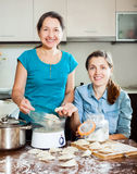 Cooking mother with adult daughter Stock Images