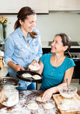 Cooking mother with adult daughter Stock Photos