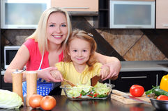 Cooking. Mother and daughter cooking dinner in kitchen Royalty Free Stock Photos