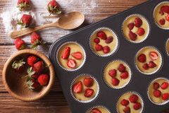 Cooking muffins with fresh strawberries horizontal top view Royalty Free Stock Image