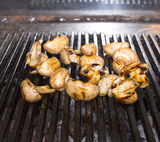 Cooking mushrooms on grill Royalty Free Stock Image