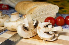 Cooking mushrooms. Mushrooms, tomatoes in the kitchen Royalty Free Stock Images