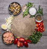 Cooking mussels shrimp tomatoes onions parsley dill garlic seasoning salt on a cutting board frame wooden background top view c Stock Photos