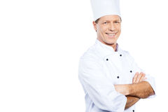 Cooking is my passion. Confident mature chef in white uniform keeping arms crossed and smiling while standing against white background Royalty Free Stock Photos