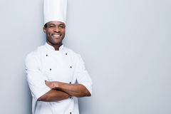 Cooking is my passion. Confident young African chef in white uniform keeping arms crossed and smiling while standing against grey background Royalty Free Stock Photo
