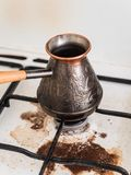 Cooking natural coffee. Coffee in Turk on the gas stove boiled away. Dirty stove. The incident in the kitchen. Cooking natural coffee. The incident in the stock images