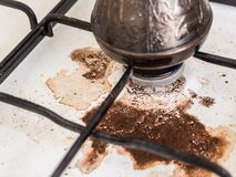 Cooking natural coffee. Coffee in Turk on the gas stove boiled away. Dirty stove. The incident in the kitchen. Cooking natural coffee. The incident in the royalty free stock photo