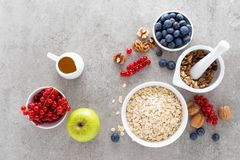 Cooking oatmeal with fresh berries, blueberry, red currant, walnuts and honey. Healthy vegetarian breakfast food concept, top view royalty free stock images