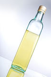 Cooking oil. A bottle of cooking oil/olive oil on a reflective surface stock image