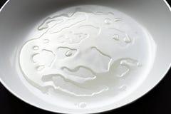 Cooking oil on white ceramic frypan. Stock Photo