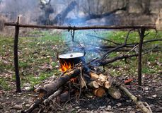 Cooking in old sooty cauldron on campfire. At forest Stock Photos