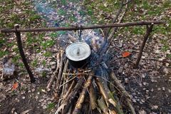 Cooking in old sooty cauldron on campfire at glade. Wide angle view from above Royalty Free Stock Images