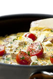 Cooking Omelet. In a pan, ready to serve. With Cherry tomatoes, red onion, goat's cheese and parsley. Shallow DOF stock photo