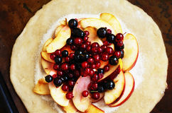 Cooking open pie or galette with apples and berries Royalty Free Stock Photography
