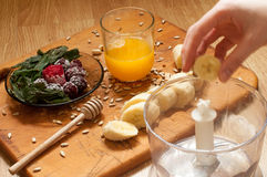 Cooking, orange juice, banana,frozen strawberries blackberries and seeds vivid smoothie ingredients and blender, juicer, tulips on. The background on wooden stock photos