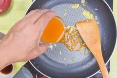 Cooking orange sauce for fish steak Royalty Free Stock Image