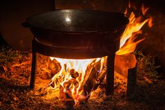 Cooking over a campfire. Camping fire and kettle with frying fish Royalty Free Stock Photos
