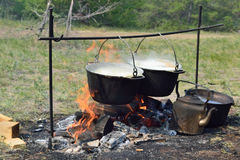 Cooking over a campfire in field conditions Stock Photos