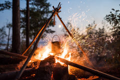 Cooking over a campfire in the woods at night. Royalty Free Stock Images