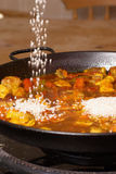 Cooking paella. Poruing rice into a paella pan, traditional cooking royalty free stock image