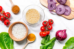 Cooking paella with vegetables and rice ingredients on white desk background top view. Cooking paella with vegetables and rice ingredients on white kitchen desk stock image