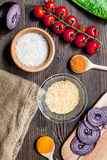 Cooking paella with vegetables, spices and rice on wooden desk background top view Royalty Free Stock Photos